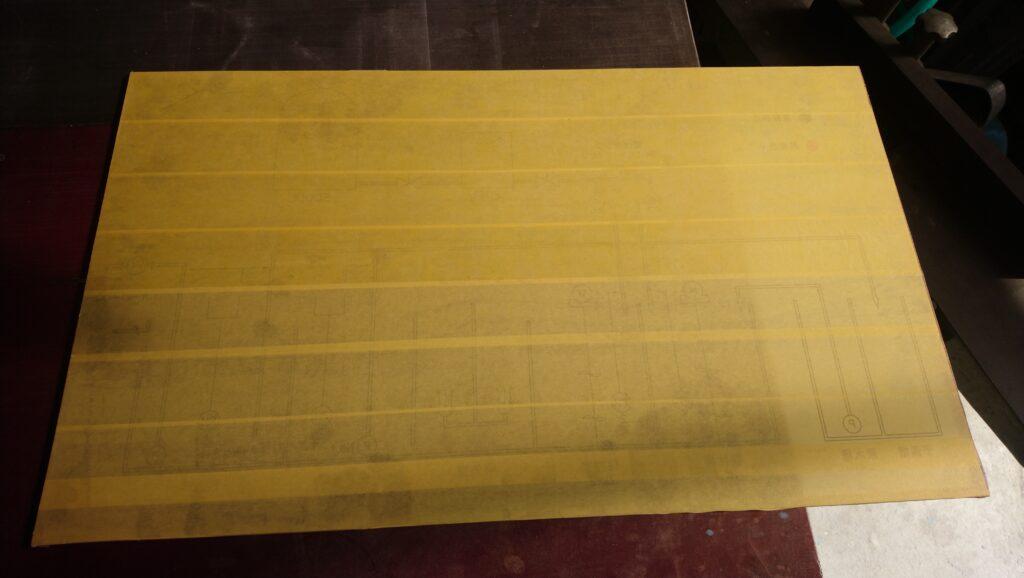 グラフィックの途中過程において紙テープを前面に貼った透明アクリル板
