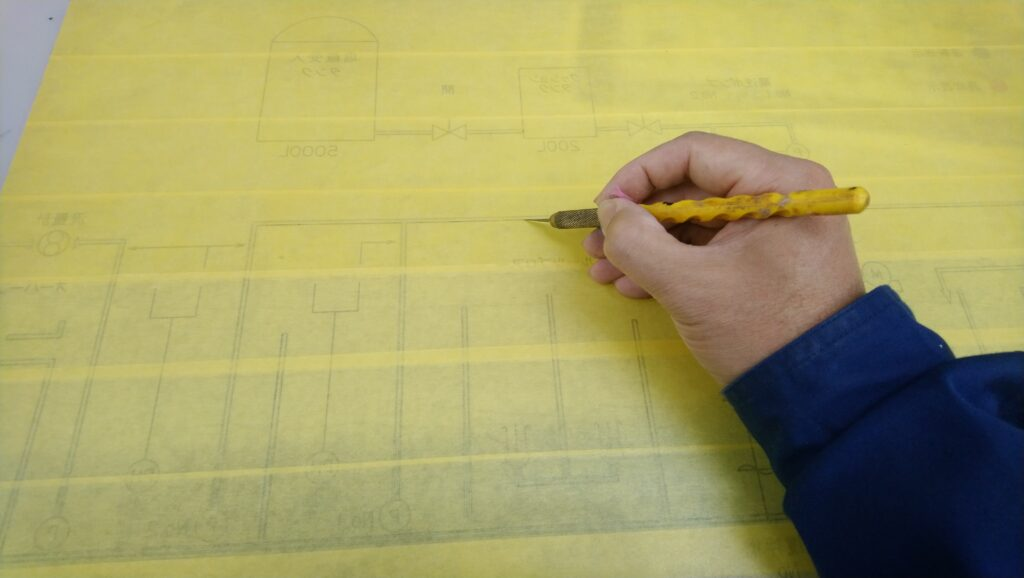 グラフィックの途中過程において裏から紙テープをデザインナイフで切っているところ